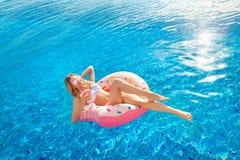 Vacanza di estate Donna in bikini sul materasso gonfiabile della ciambella nella piscina della STAZIONE TERMALE fotografia stock libera da diritti