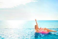 Vacanza di estate Donna in bikini sul materasso gonfiabile della ciambella nella piscina della STAZIONE TERMALE fotografia stock