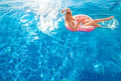 Vacanza di estate Donna in bikini sul materasso gonfiabile della ciambella nella piscina della STAZIONE TERMALE immagini stock