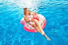 Vacanza di estate Donna in bikini sul materasso gonfiabile della ciambella nella piscina della STAZIONE TERMALE immagine stock