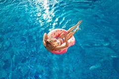 Vacanza di estate Donna in bikini sul materasso gonfiabile della ciambella nella piscina della STAZIONE TERMALE fotografie stock libere da diritti