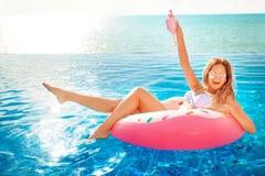 Vacanza di estate Donna in bikini sul materasso gonfiabile della ciambella nella piscina della STAZIONE TERMALE Viaggio al resto  fotografia stock libera da diritti