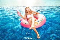 Vacanza di estate Donna in bikini sul materasso gonfiabile della ciambella nella piscina della STAZIONE TERMALE Viaggio al resto  fotografie stock libere da diritti