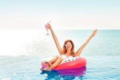 Vacanza di estate Donna in bikini sul materasso gonfiabile della ciambella nella piscina della STAZIONE TERMALE Viaggio sulla spi immagini stock