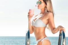 Vacanza di estate Donna in bikini sul materasso gonfiabile nella piscina della STAZIONE TERMALE con coctail immagini stock libere da diritti