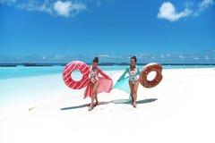 Vacanza di estate Due donne libere felici con il materasso gonfiabile del galleggiante della ciambella Ragazze che indossano gode immagini stock libere da diritti