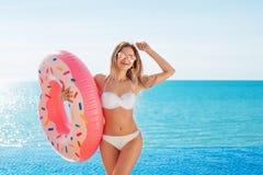 Vacanza di estate Godere della donna di abbronzatura in bikini bianco con il materasso della ciambella vicino alla piscina immagine stock libera da diritti