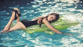 Vacanza di estate Godere della donna di abbronzatura in bikini sul materasso gonfiabile nella piscina fotografia stock