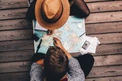 Vacanza di pianificazione delle coppie facendo uso della mappa di mondo fotografia stock libera da diritti