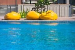 Vacanza e concetto di rilassamento: Materasso giallo tre sul bordo della piscina nella località di soggiorno Fotografia Stock Libera da Diritti
