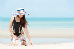 Vacanza estiva Viaggi d'uso sorridenti di estate di modo del bikini della donna asiatica di stile di vita che si siedono e che gi immagine stock libera da diritti