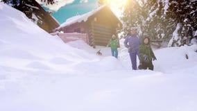 Vacanza felice di inverno di spesa della famiglia nella cabina della montagna con il loro cane archivi video