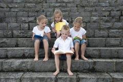 Vacanze estive: bambini con un libro messo all'aperto sulle scale Fotografie Stock Libere da Diritti