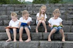 Vacanze estive: bambini con un libro messo all'aperto sulle scale Immagini Stock