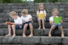Vacanze estive: bambini con un libro messo all'aperto sulle scale Immagini Stock Libere da Diritti
