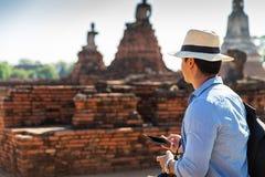 Vacanze estive dell'Asia orientale Turista caucasico dell'uomo dalla parte posteriore che esamina il tempio di Wat Chaiwatthanara immagine stock libera da diritti