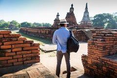 Vacanze estive dell'Asia orientale Turista caucasico dell'uomo dalla parte posteriore che esamina il tempio di Wat Chaiwatthanara immagini stock libere da diritti