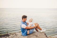 Vacanze estive della famiglia in natura il padre e la piccola figlia si siedono sulla scogliera sabbiosa per un anno con l'alta v Immagini Stock Libere da Diritti