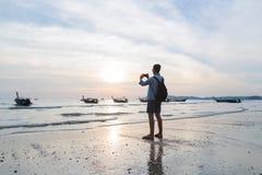 Vacanze estive della spiaggia dell'uomo, giovane retrovisione di Guy Take Photo Sunset Back Immagine Stock