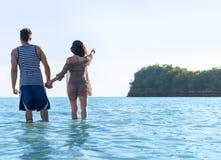 Vacanze estive della spiaggia delle coppie, donna dell'uomo in dito del punto di acqua per copiare spazio bello giovane Guy Girl  Fotografia Stock