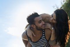 Vacanze estive della spiaggia delle coppie, uomo di Carry Woman Beautiful Young Happy dell'uomo e sorriso della donna Immagine Stock Libera da Diritti