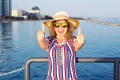 Vacanze estive e vacanza - giovane donna che mostra i pollici su sulla spiaggia Immagine Stock