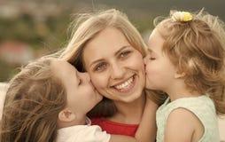 Vacanze estive, svago, attività, stile di vita Madre di bacio delle figlie su paesaggio naturale Fotografia Stock