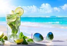 Vacanze estive tropicali; Bevande esotiche sul BAC tropicale della spiaggia della sfuocatura immagini stock libere da diritti