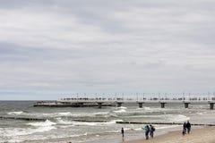 Vacanzieri su una spiaggia di sabbia durante il giorno ventoso Fotografie Stock Libere da Diritti