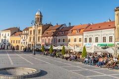 Vacanzieri sul quadrato centrale del Brasov anziano in Romania immagini stock libere da diritti