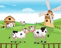 Vacas en la cumbre con un molino de viento ilustración del vector