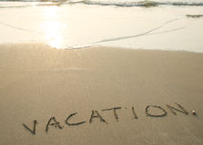 Vacation. Word vacation is writ on the sand of the beach Stock Photography