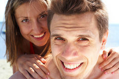 At vacation. Photo of smiling guy looking at camera while pretty woman behind embracing him Royalty Free Stock Images