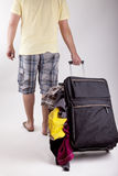 Vacation. Studio shot of a man walking with a suitcase and loosing the luggage Royalty Free Stock Images