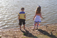 Vacation. Two young kids are hanging out near the water front on a late summer afternoon Royalty Free Stock Photography