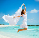 Vacation. Beautiful Girl With White Scarf Jumping on The Beach. Travel and Vacation. Freedom Concept Stock Photos