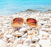 Vacation. Sunglasses on the beach with pebbles. The sea in the background stock photos