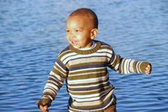 Vacation. Here is a young boy in his fall clothes by the water Royalty Free Stock Photography
