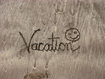 Vacation. The word 'vacation' inscribed with a smiley on beach sands Stock Photography