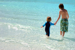On Vacation. Two boys enter the water holding hands Royalty Free Stock Images