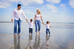 Vacation. Family walking on a beach, all wearing jeans and white shirts Royalty Free Stock Images