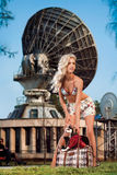 On vacation. A pretty sexy blonde with a pocket dog in a bag in front of radar station Stock Images