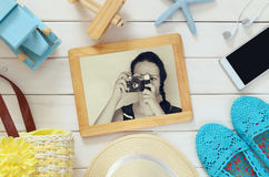 Vacation accessories and toys next to young girl photography. Top view of vacation accessories and toys next to photoframe with young girl photography  on white Royalty Free Stock Images