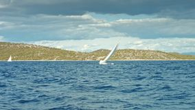 Sailboat floating on the sea. Coastline in background stock video footage