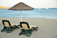 Vacation at Aegean Sea. Umbrella, two deckchairs. Blue Aegean Sea in Bagla, Turkey. Beach, water and ship Royalty Free Stock Images