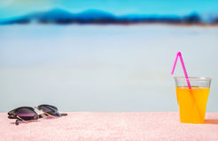 Vacation background with free blank copy space. Sunglasses and yellow cocktail with pink straw on beach. Royalty Free Stock Image