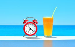 Vacation background. It`s time to travel concept. It`s time to rest. Orange fresh juice and red alarm clock standing on the tabl. E on a sea water backdrop royalty free stock photo