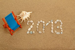 Vacation background with sun lounger and text 2013 from stones Royalty Free Stock Photography