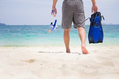 Vacation Backside of man holding snorkeling gear on tropical on. The beach on summer travel destination Royalty Free Stock Photo