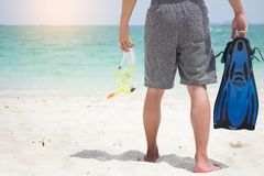 Vacation Backside of man holding snorkeling gear on tropical on. The beach on summer travel destination Royalty Free Stock Image